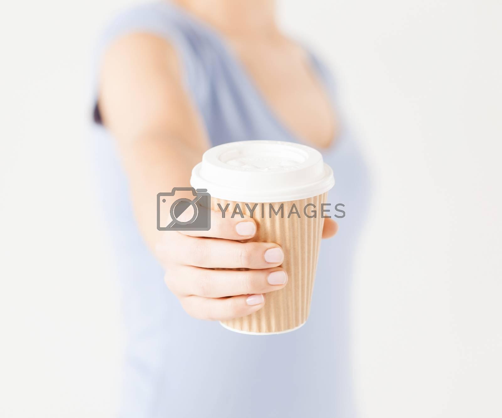 woman hand holding take away coffee cup by dolgachov