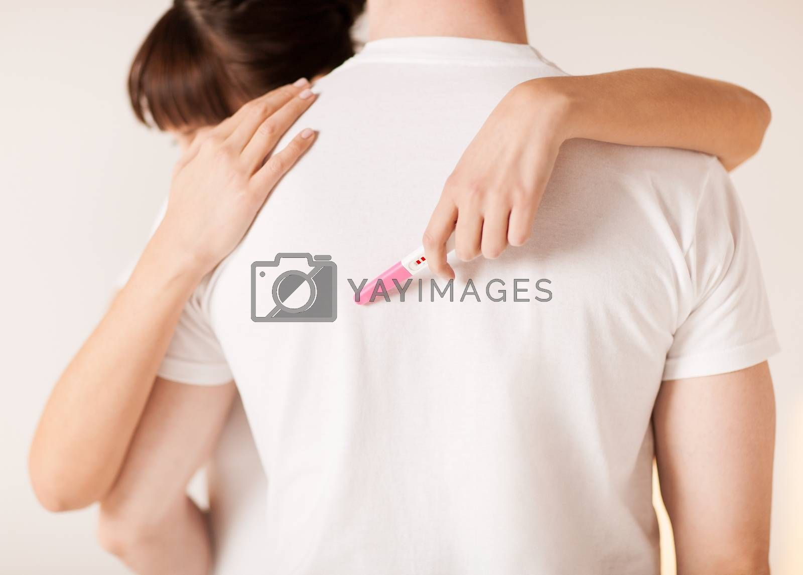 woman with pregnancy test hugging man by dolgachov