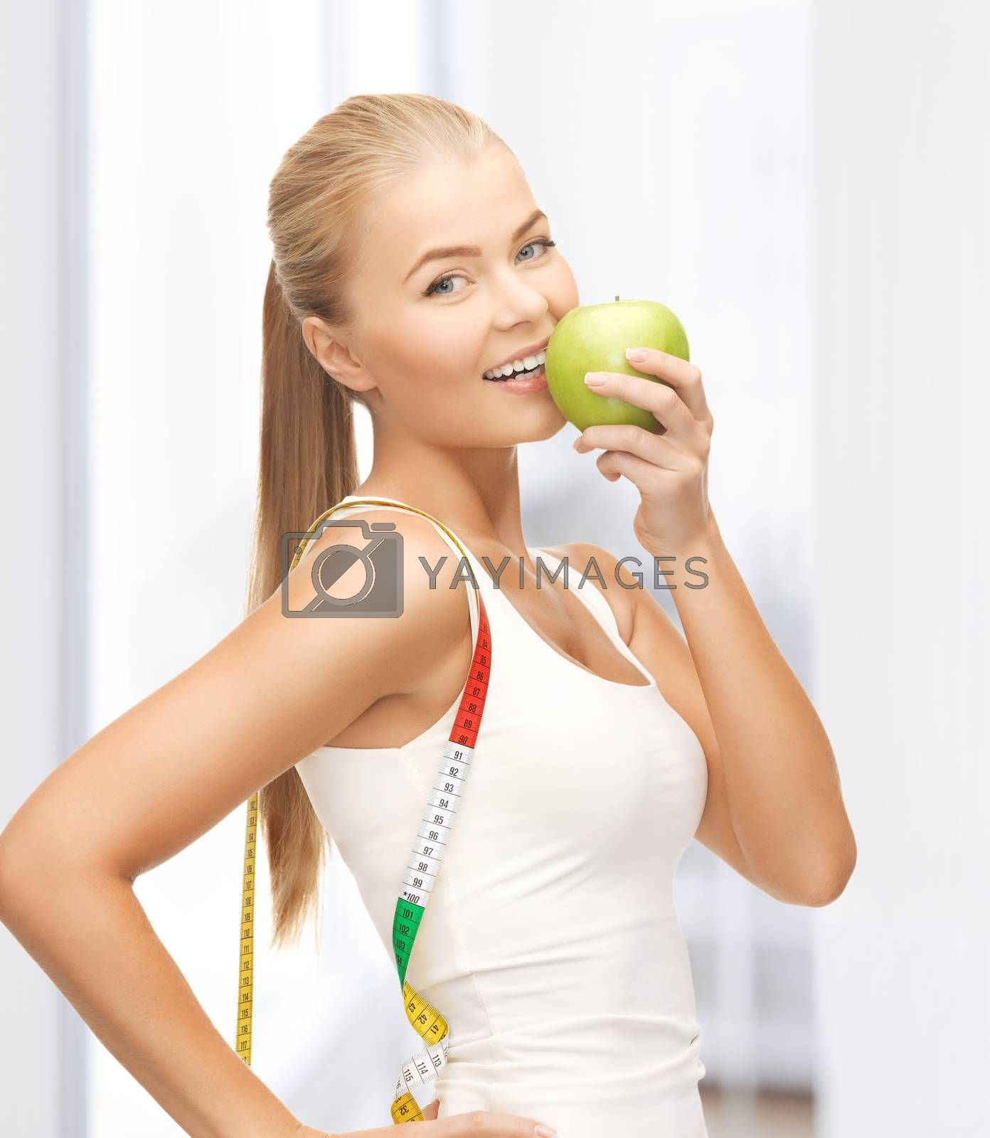 sporty woman with apple and measuring tape by dolgachov