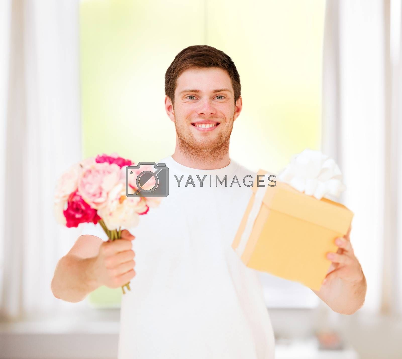 presents, gifts and celebration - man holding bouquet of flowers and gift box