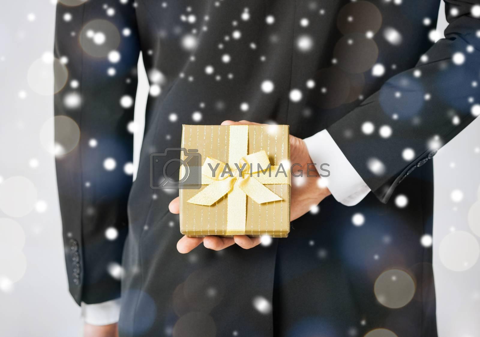 love, romance, holiday, celebration concept - man hiding gift box