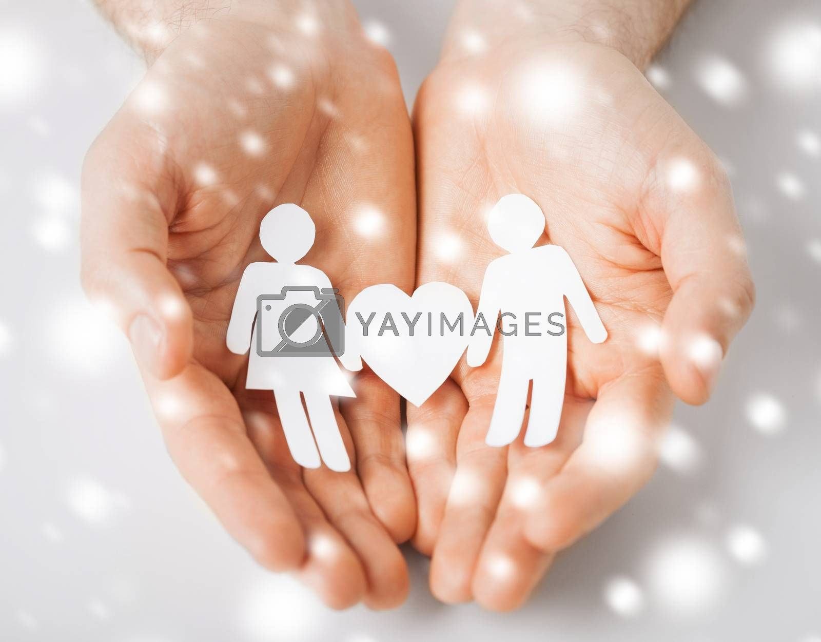 love, romance, safety concept - man hands showing two paper people with heart shape