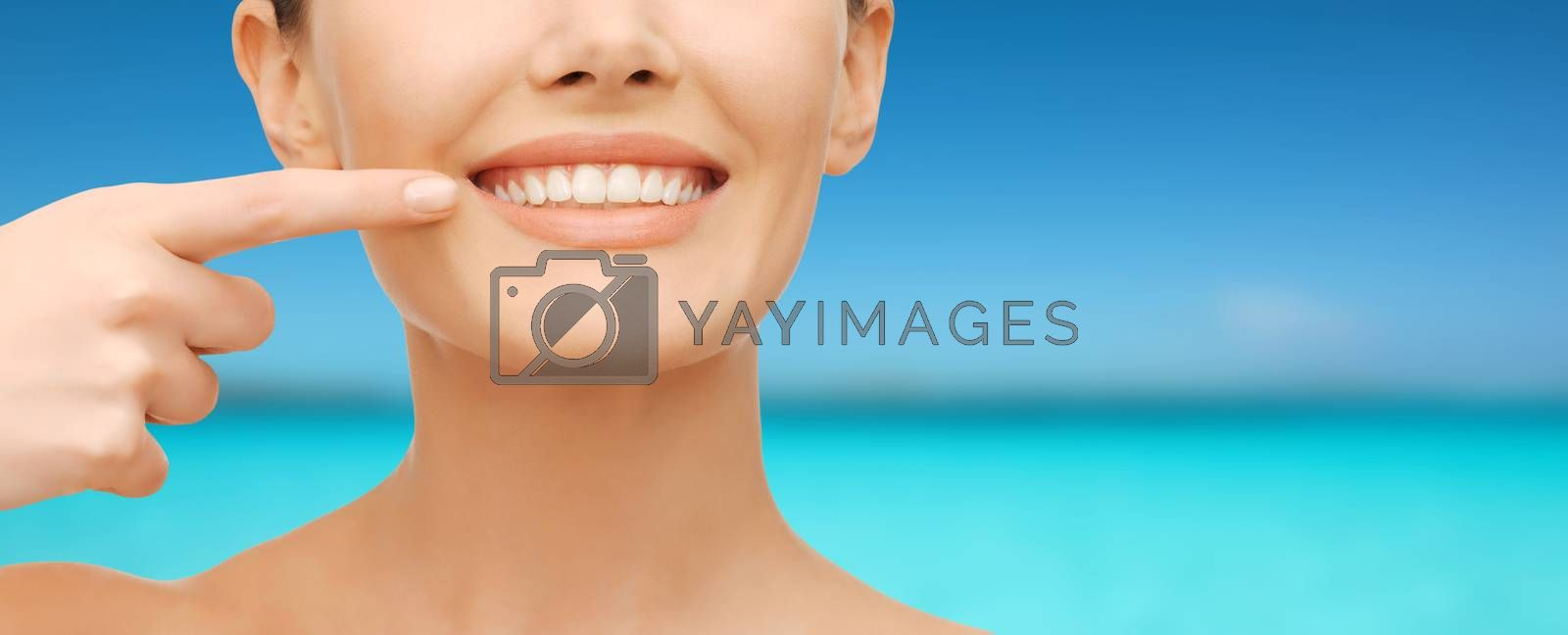 beautiful woman pointing to teeth by dolgachov