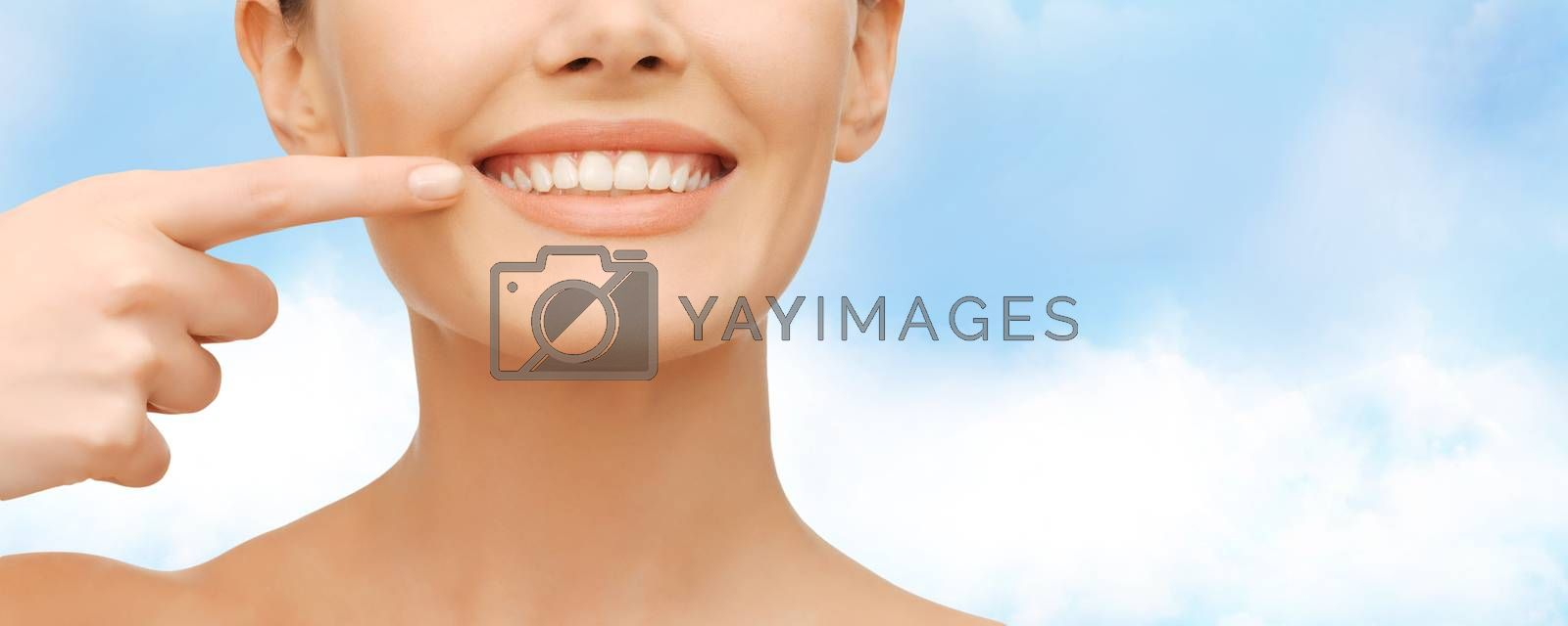 beautiful woman pointing to teeth by dolgachov