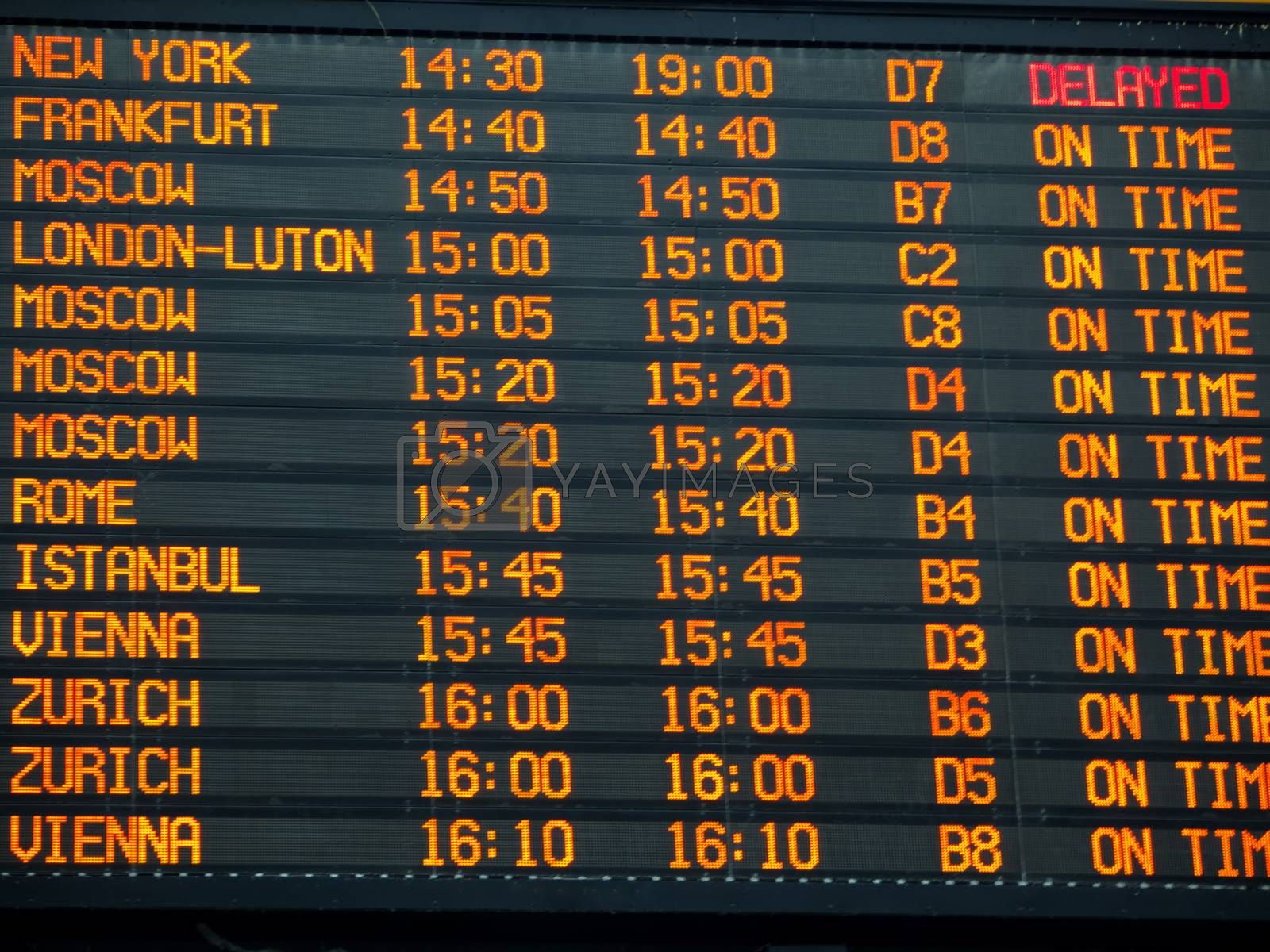 Flights information board with arrivals and departures details  in an international  airport terminal