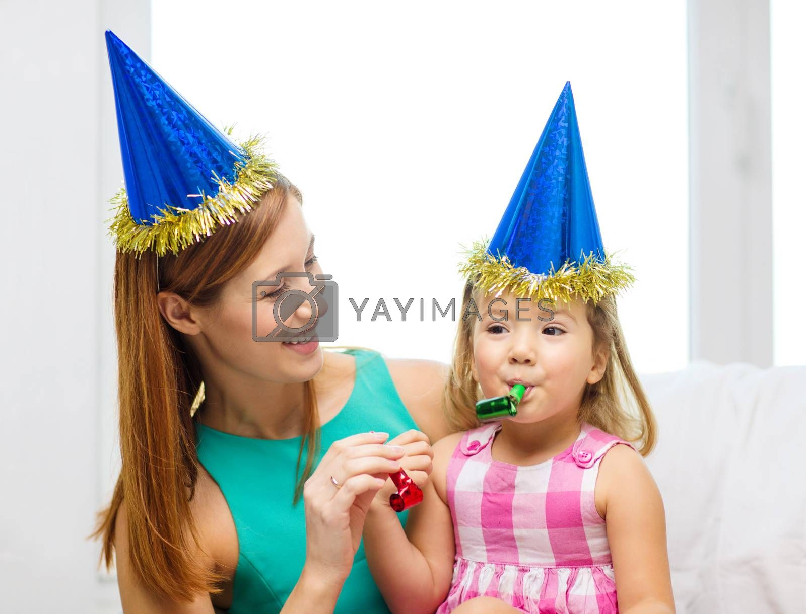 family, children, celebration and happy people concept - happy mother and daughter in blue party hats with favor horns