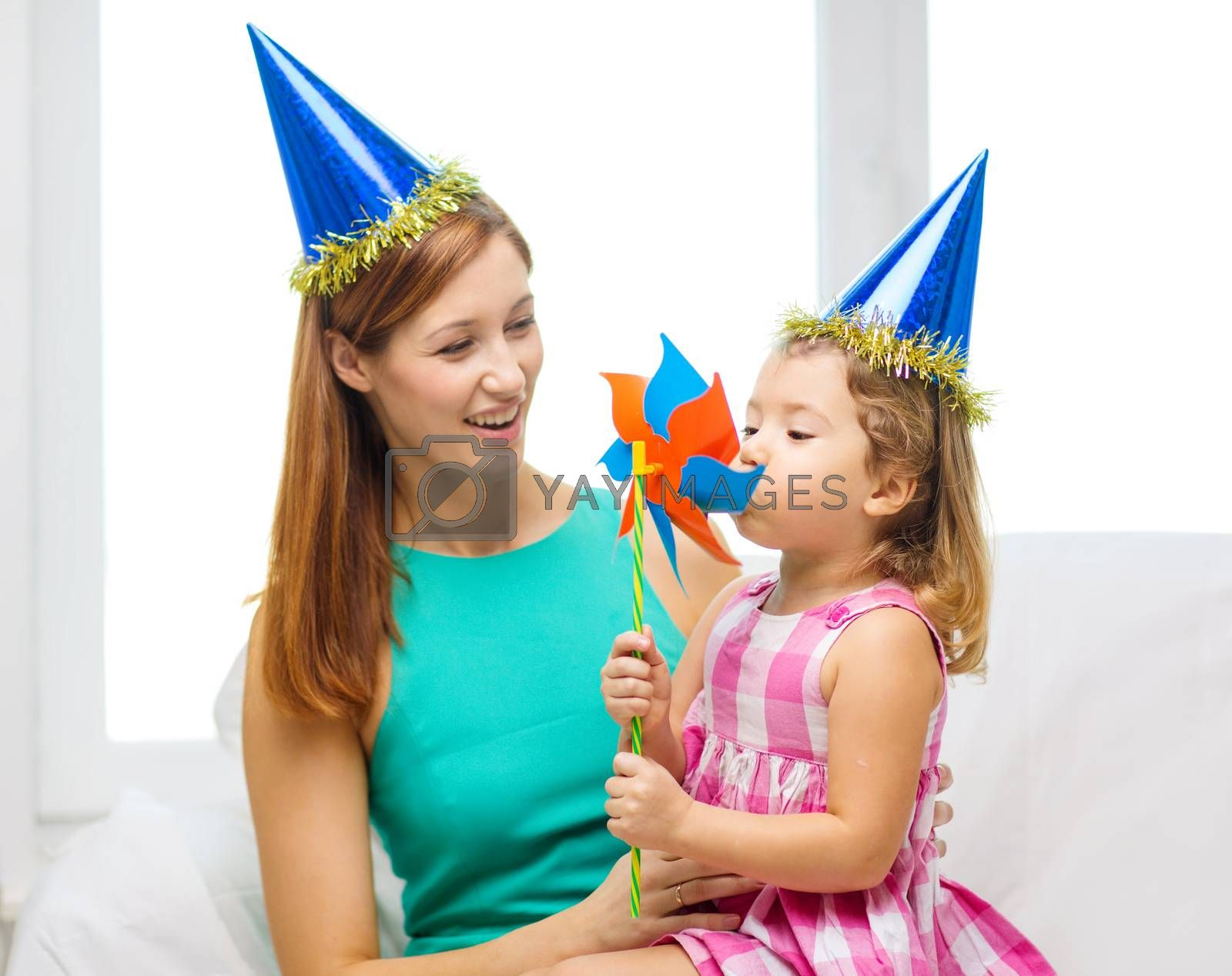 family, children, celebration and happy people concept - happy mother and daughter in blue hats with pinwheel