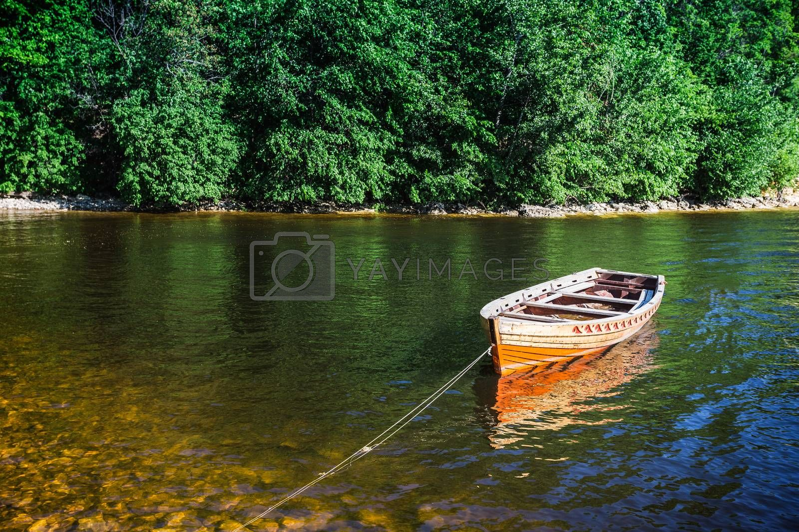 wooden boat on the river bank on forest background and blue sky reflecting in the surface of the river.
