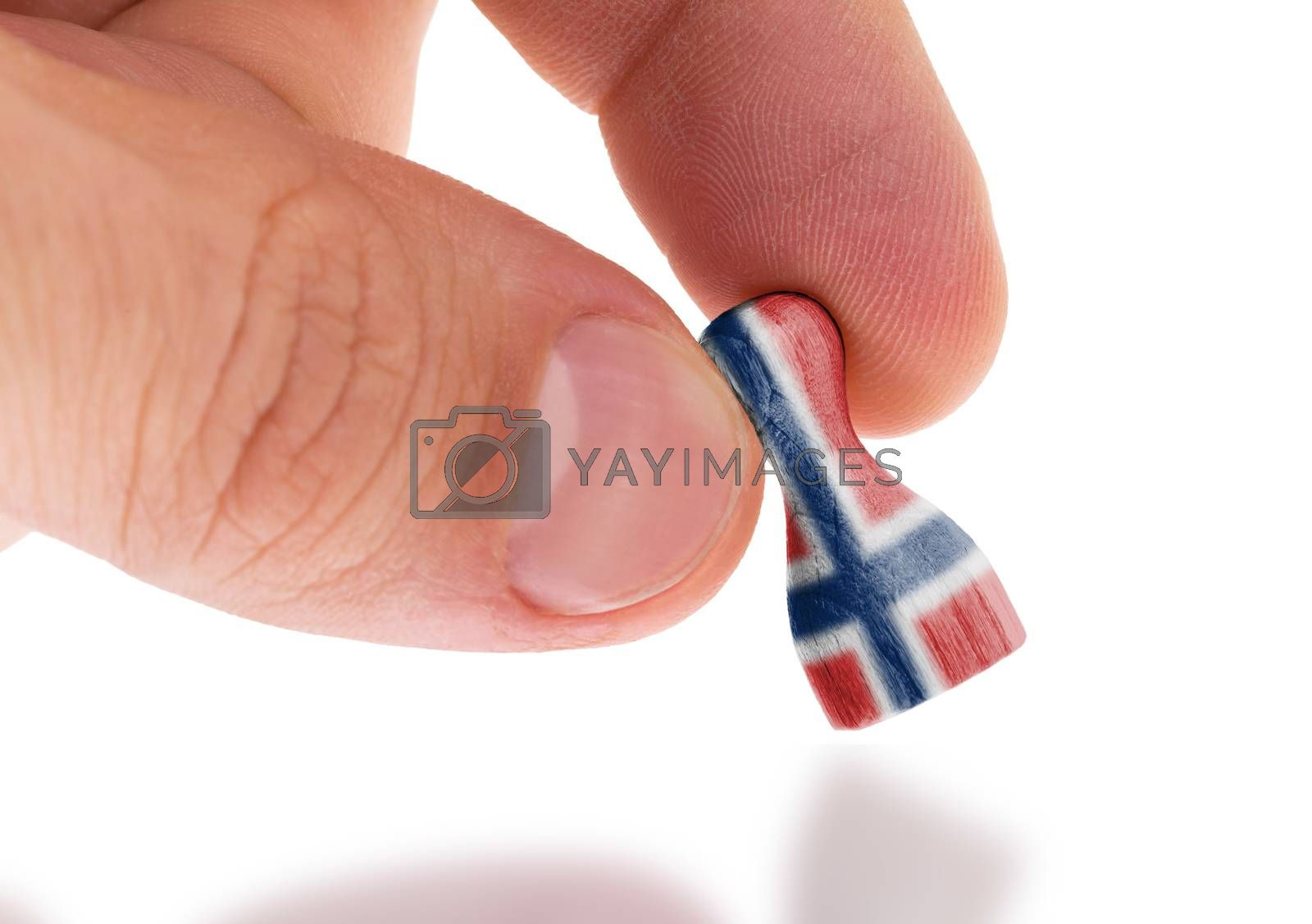Royalty free image of Hand holding wooden pawn, flag painting, selective focus by michaklootwijk