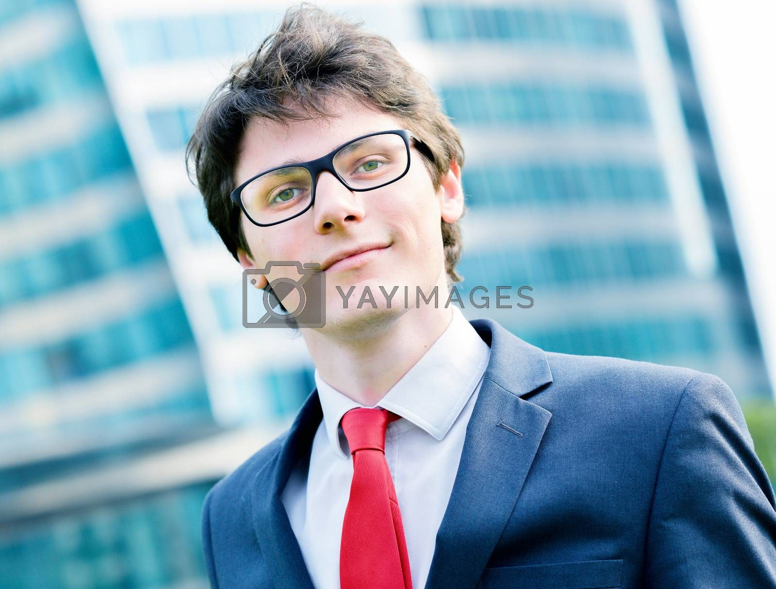 Royalty free image of Outdoor portrait of a dynamic junior executive smiling by pixinoo