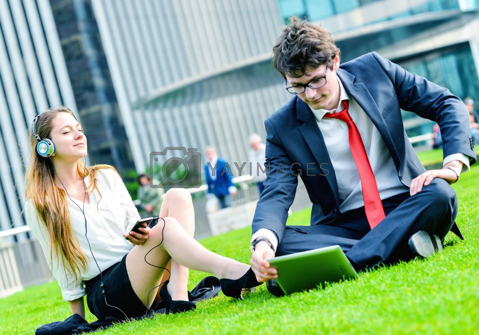 Royalty free image of Successful Junior executives dynamics laying down on green grass by pixinoo