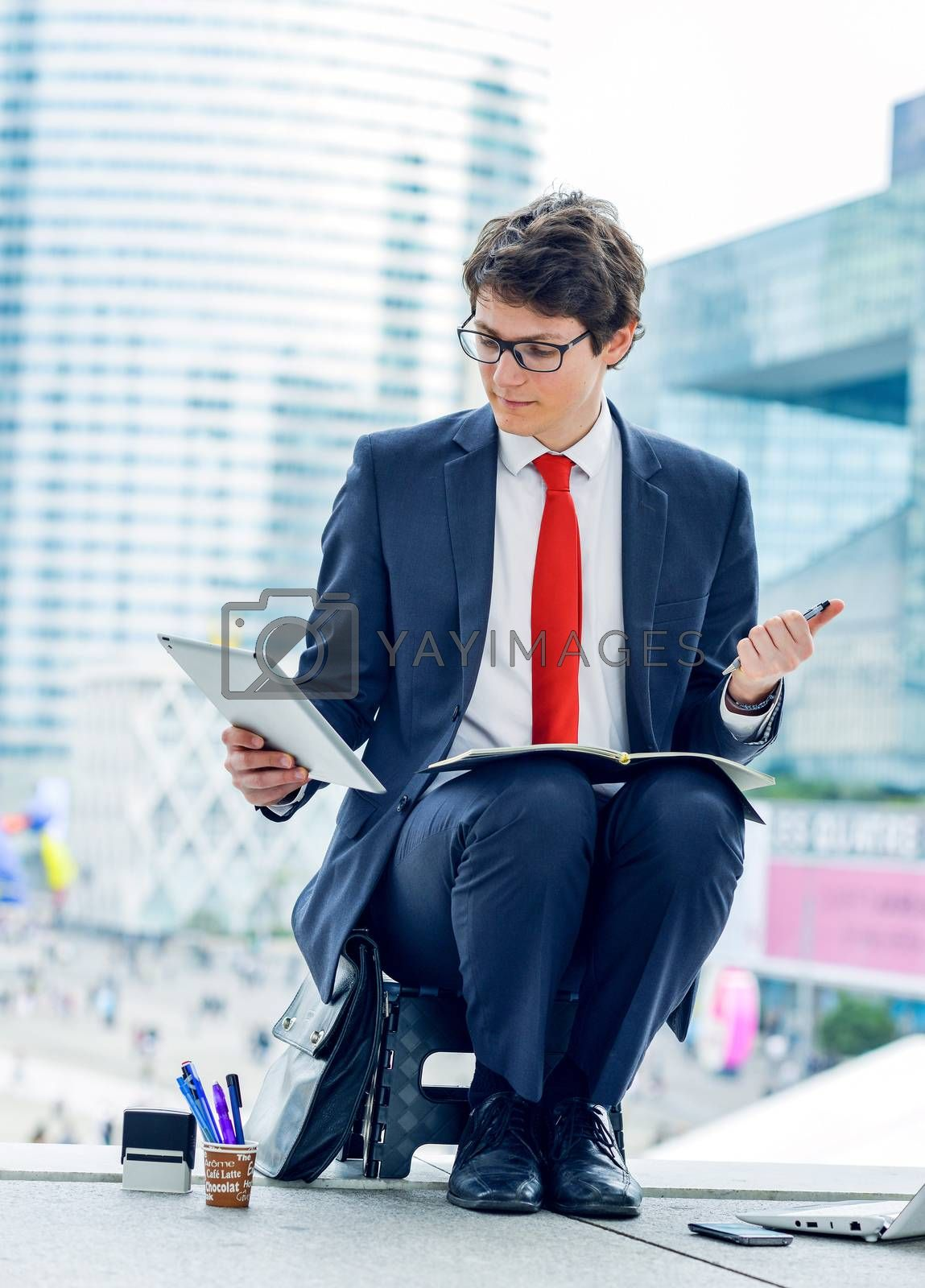 Royalty free image of Junior executive dynamic working outside of his office by pixinoo