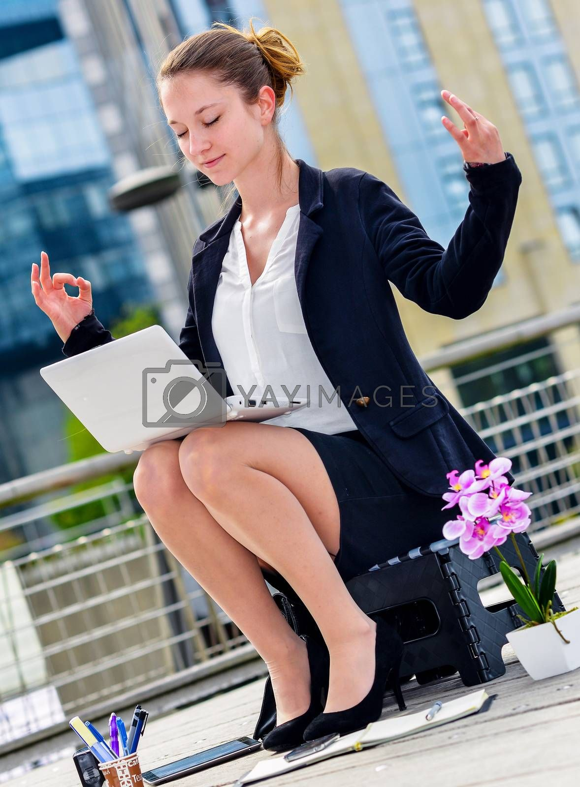 Royalty free image of Junior executive of company doing yoga for relaxation by pixinoo
