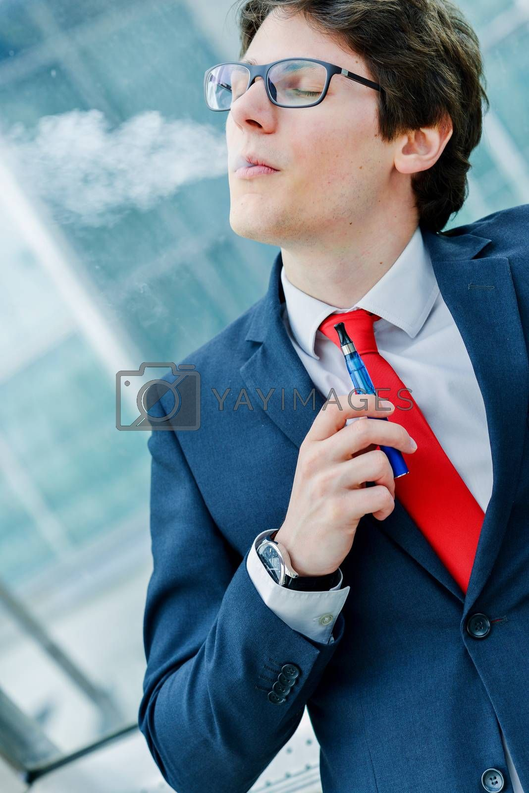 Royalty free image of Cute young adult man inhaling from an electronic cigarette by pixinoo