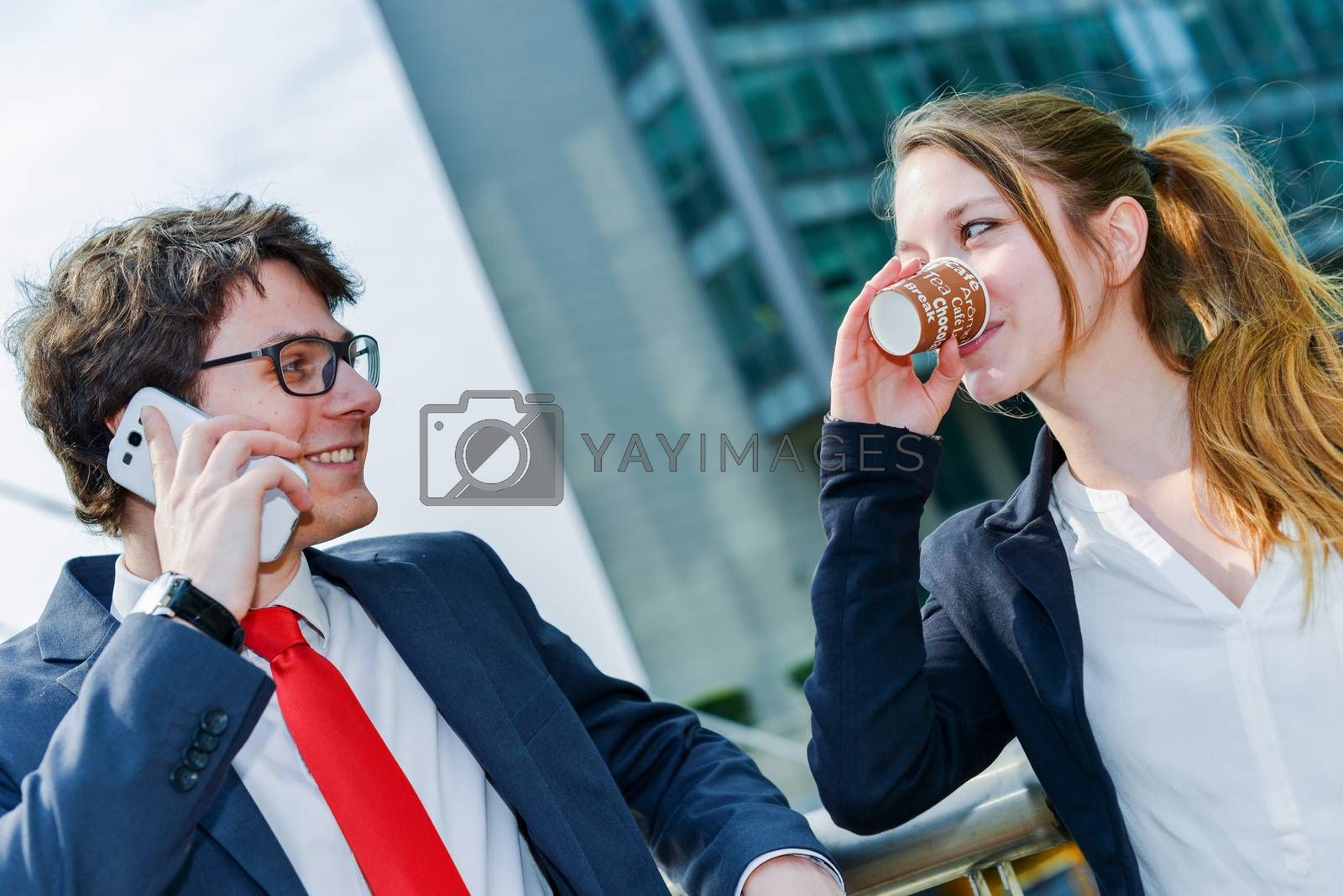 Royalty free image of Junior executives having a coffee break in front of their company by pixinoo