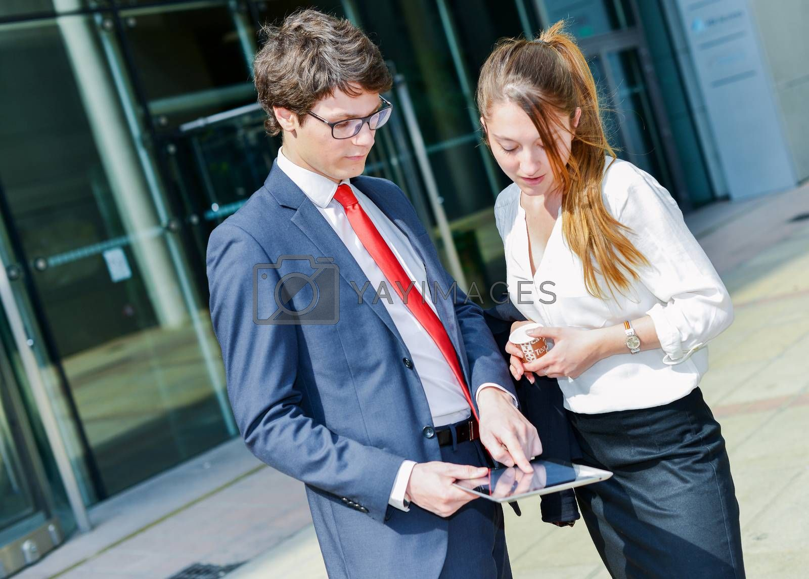 Royalty free image of Junior executives consulting a touchpad in front of their company by pixinoo