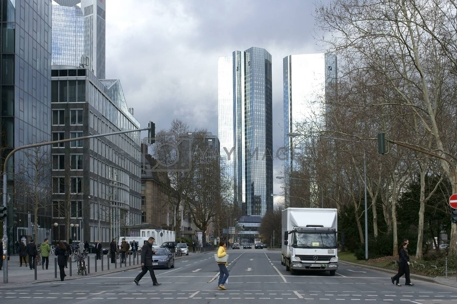 Frankfurt, Germany - February 19, 2014: Pedestrians cross a traffic light intersection with the high-rise building of the Deutsche Bank at the end of the street on February 19, 2014 in Frankfurt.