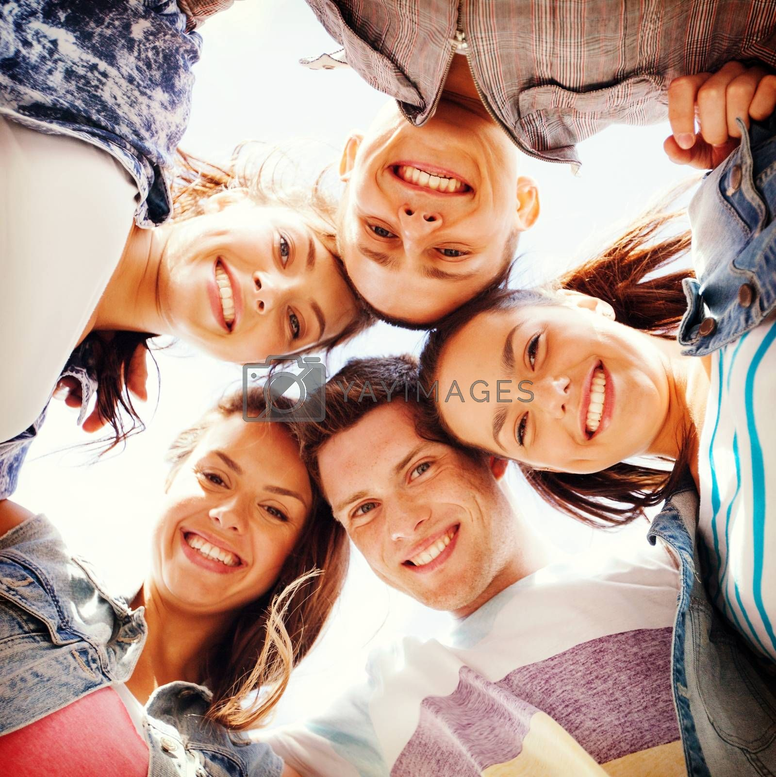 summer holidays and teenage concept - group of teenagers looking down