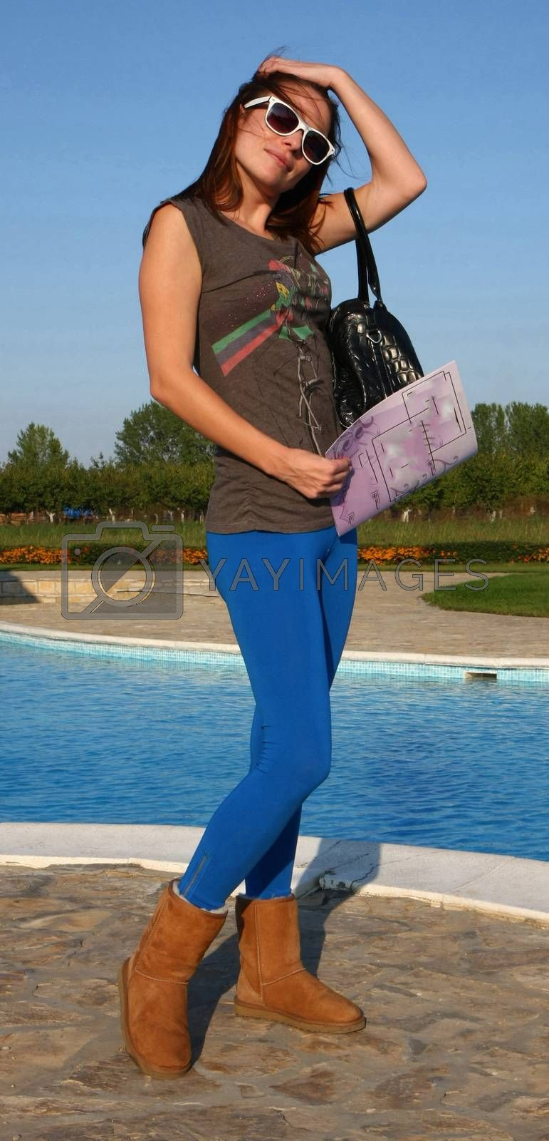 Young woman posing in front of swimming pool