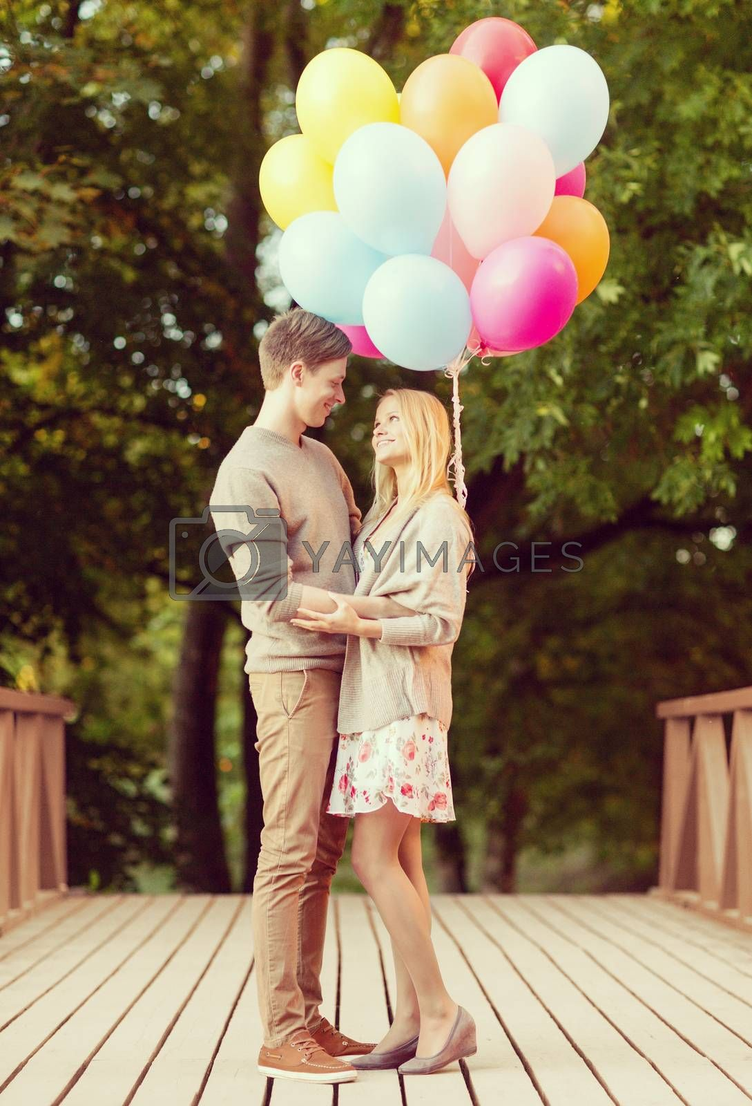 summer holidays, celebration and dating concept - couple with colorful balloons in the park