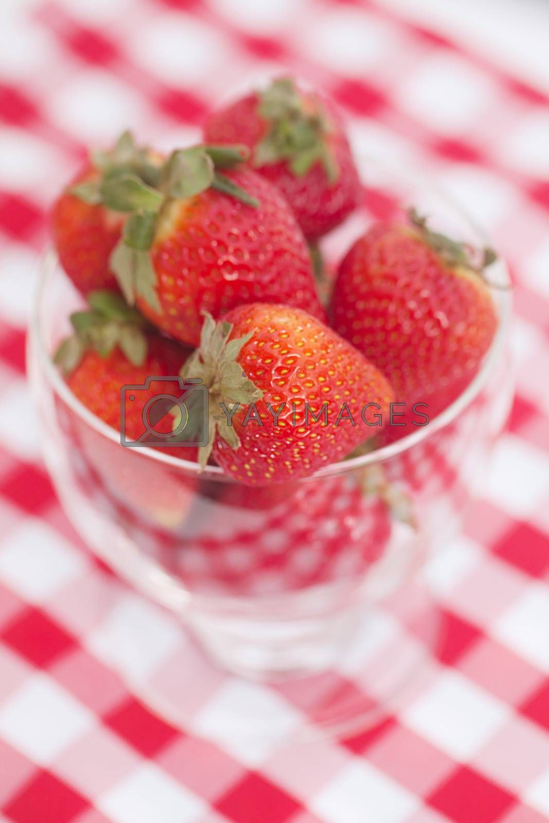 strawberry in a glass bowl on checkered fabric