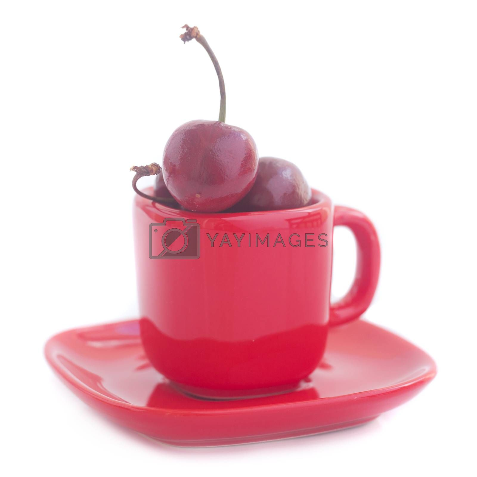 Cherries in red cup isolated on white