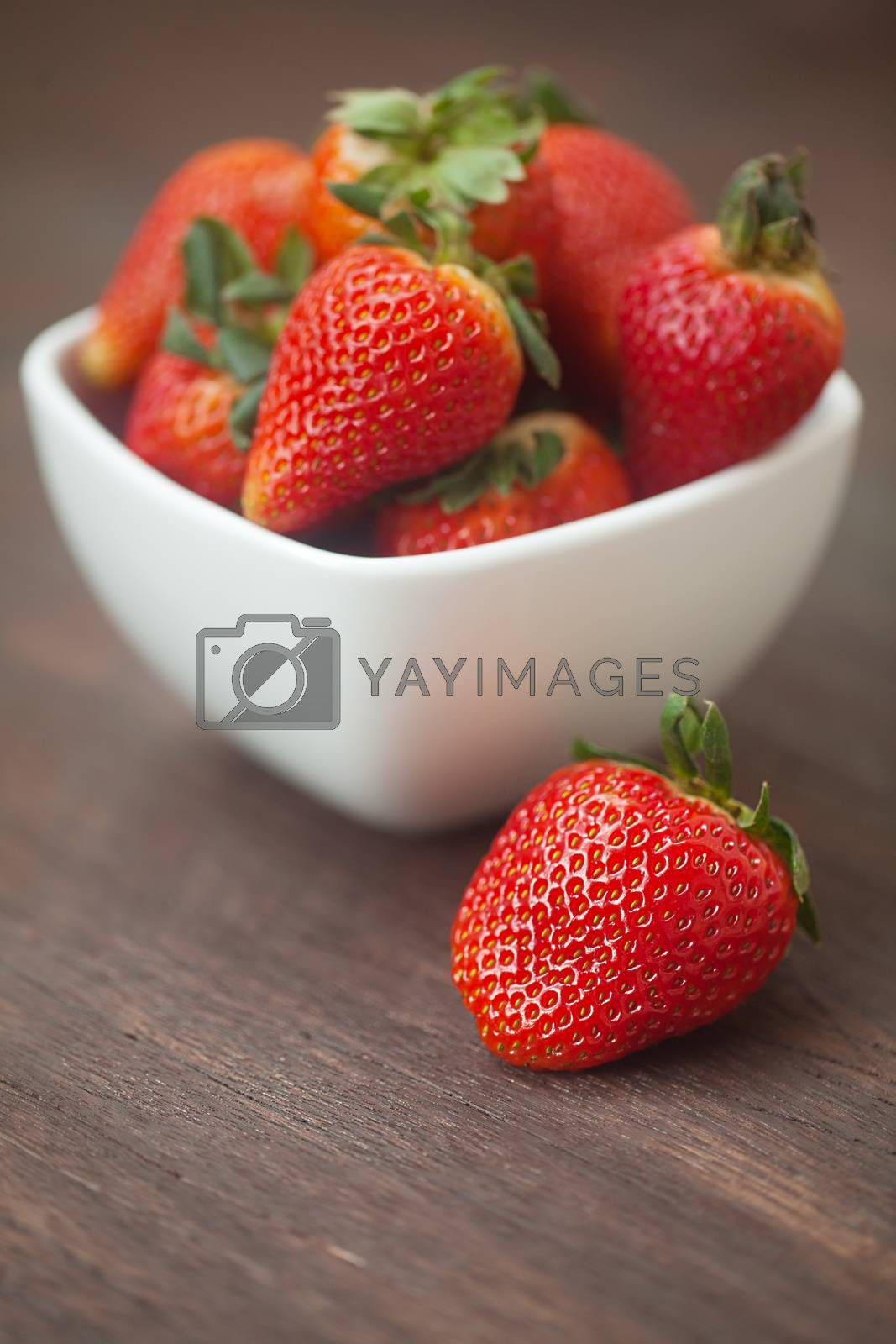 red juicy strawberry in a bowl on a wooden surface