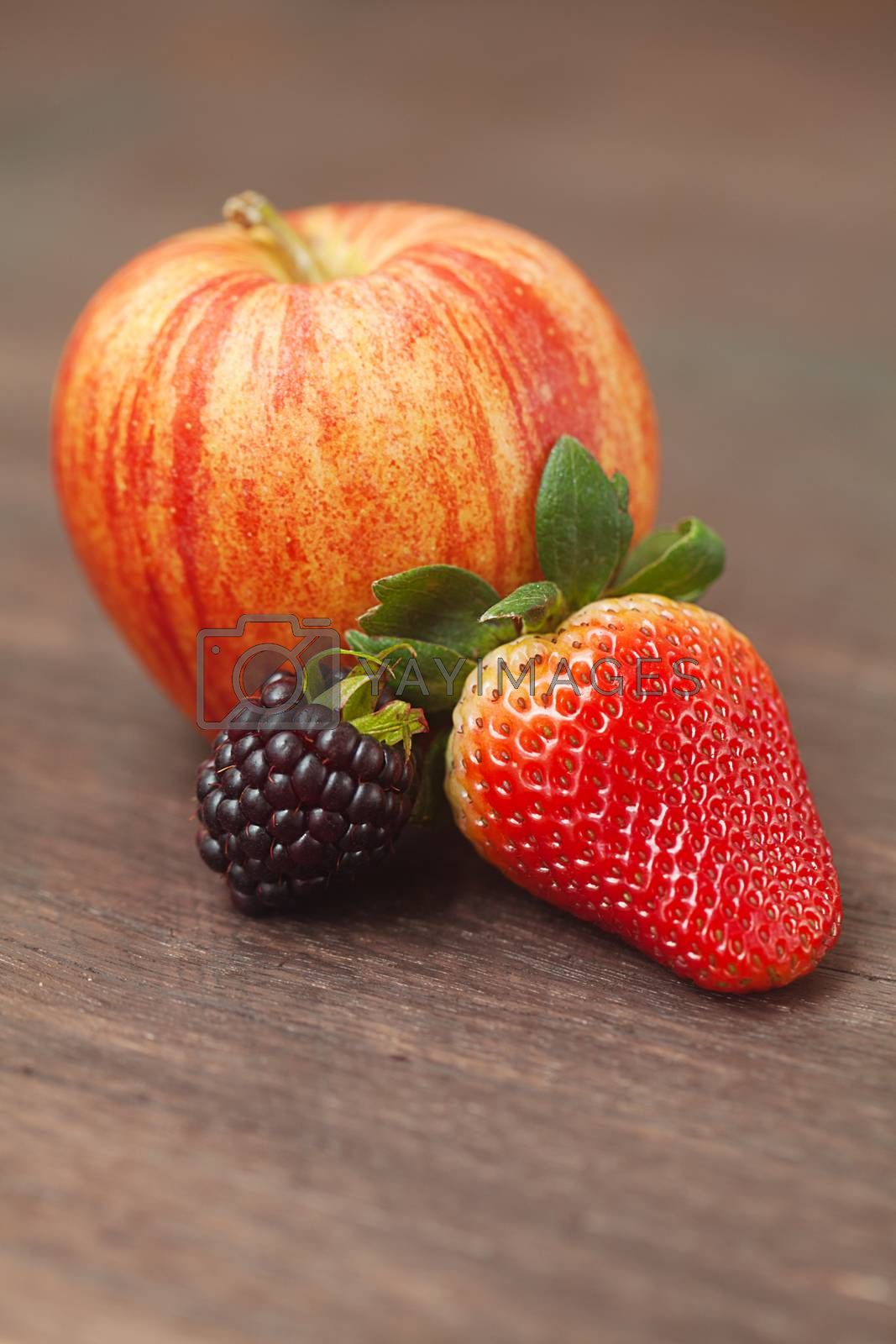 juicy apple,blackberry and strawberry on a wooden surface