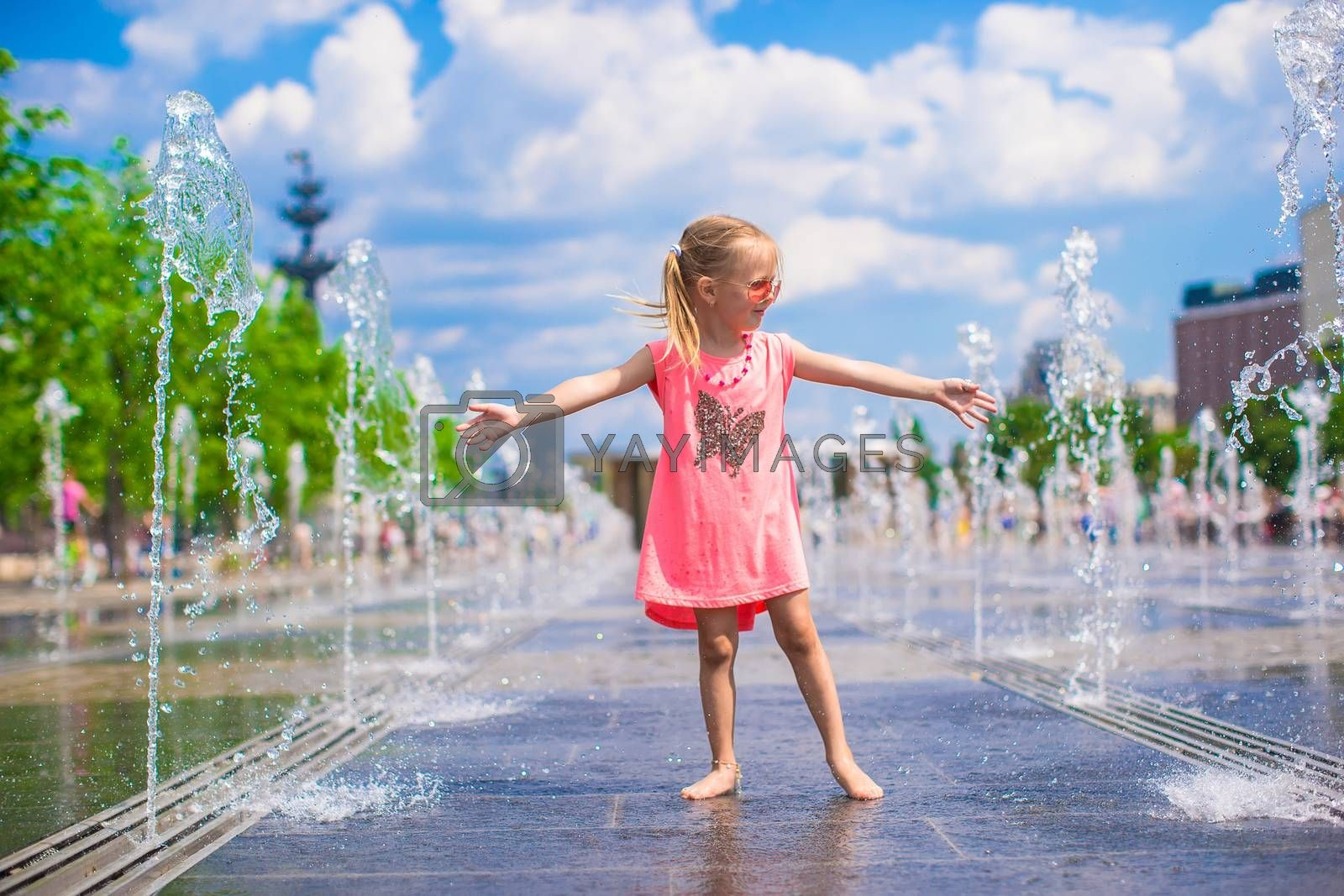 Adorable little girl playing in street fountain