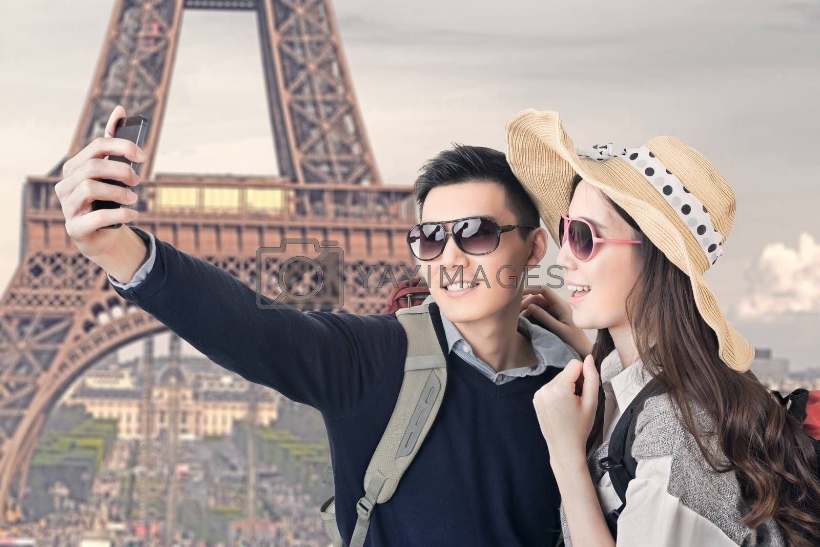 Asian couple travel and take a selfie at Eiffel Tower, Paris, France.