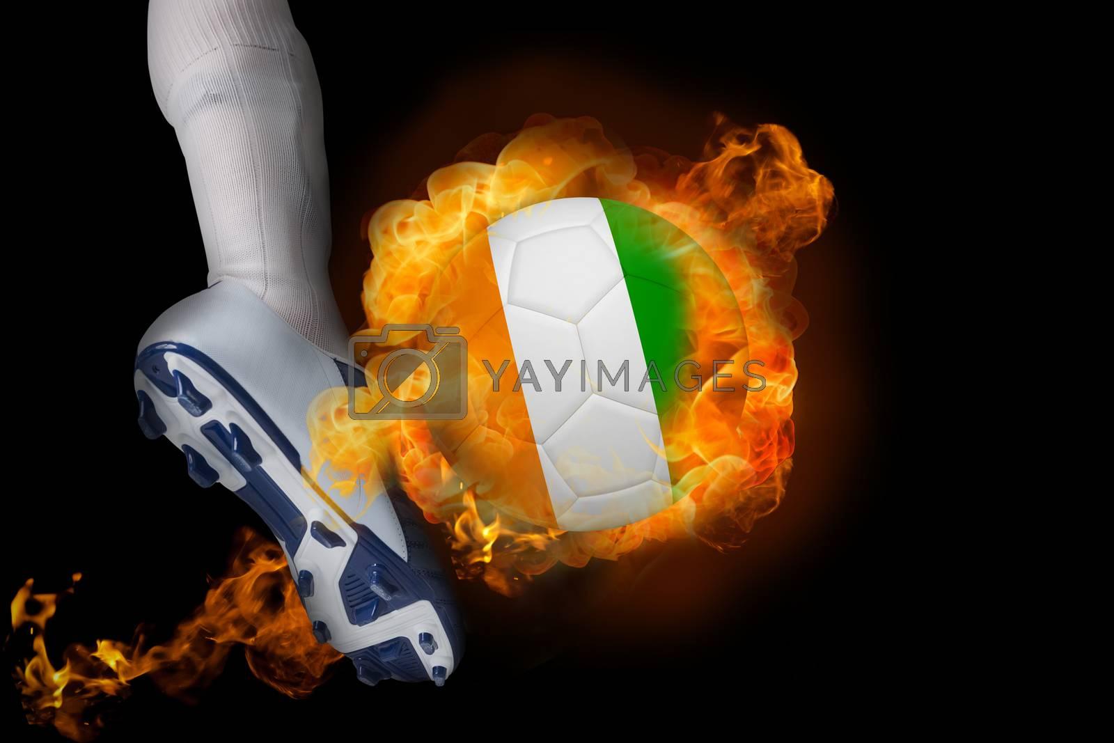 Football player kicking flaming ivory coast ball by Wavebreakmedia