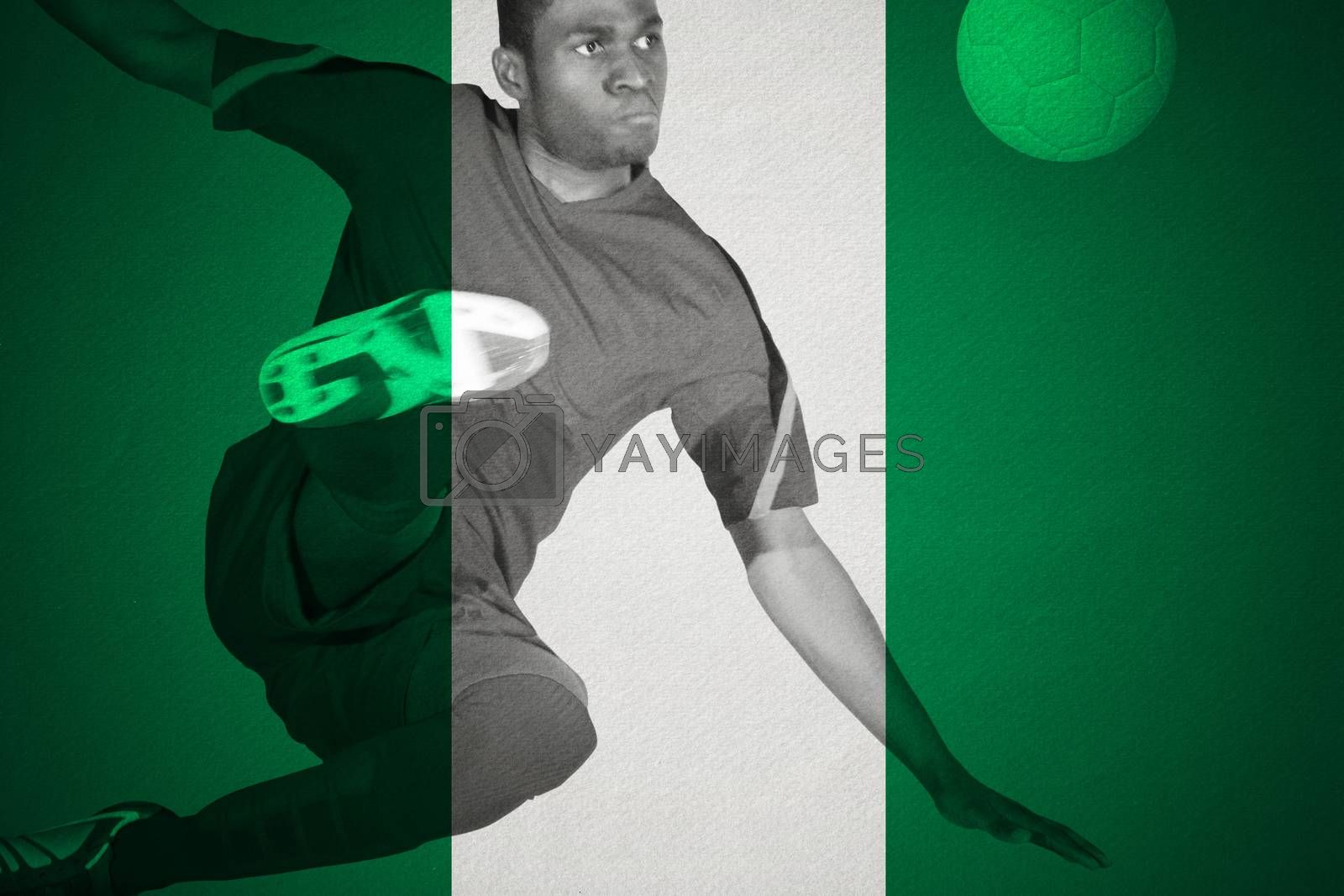 Football player in green kicking by Wavebreakmedia