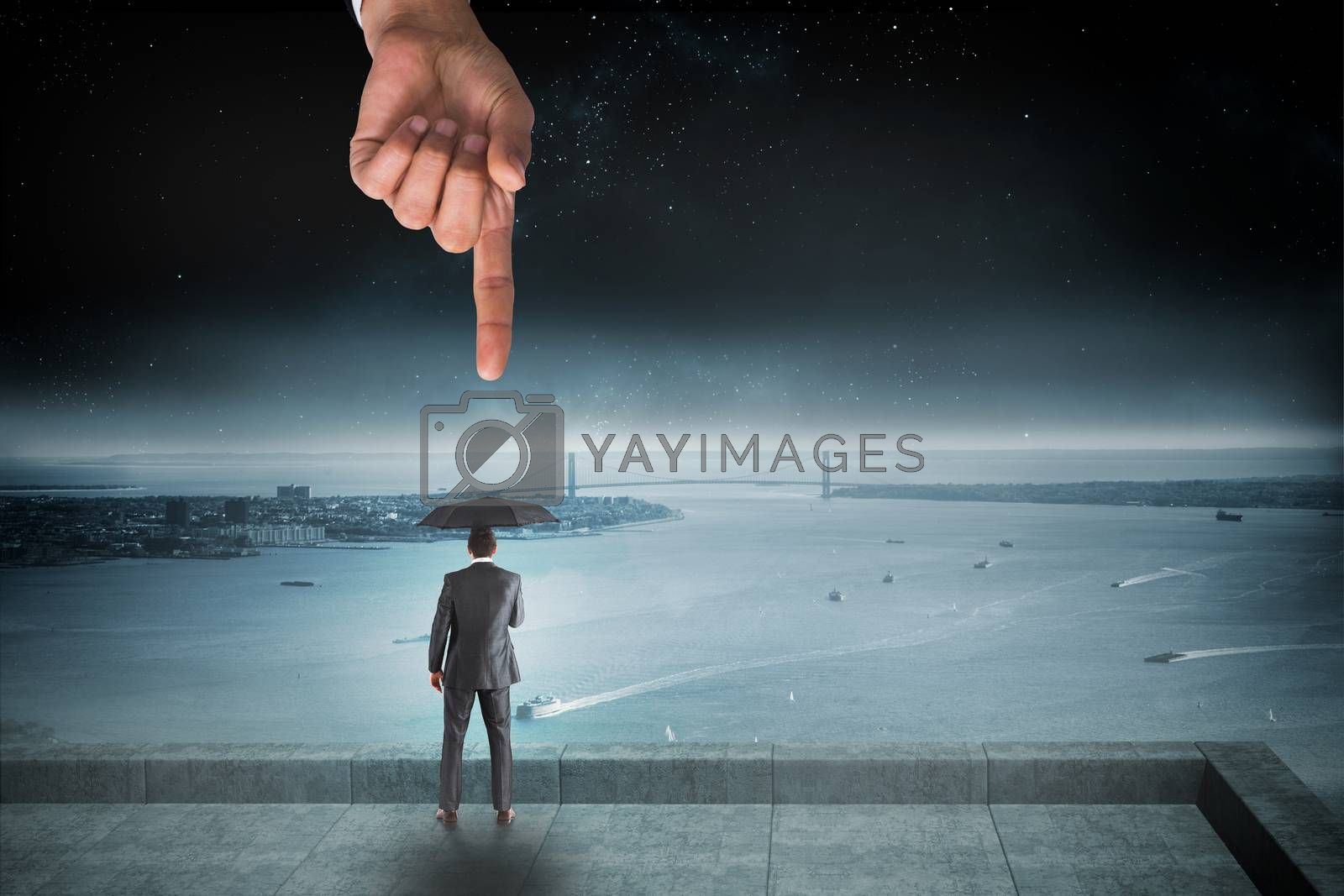 Giant hand pointing at businessman holding an umbrella by Wavebreakmedia