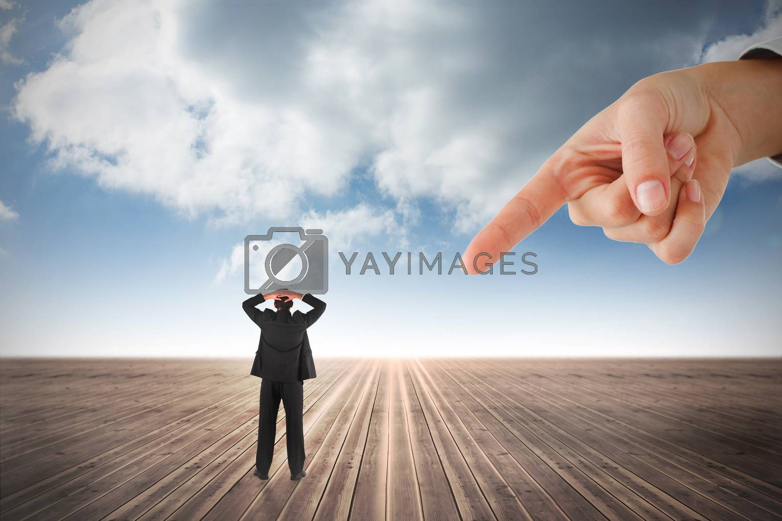 Giant hand pointing at businessman standing back to the camera with hands on head by Wavebreakmedia