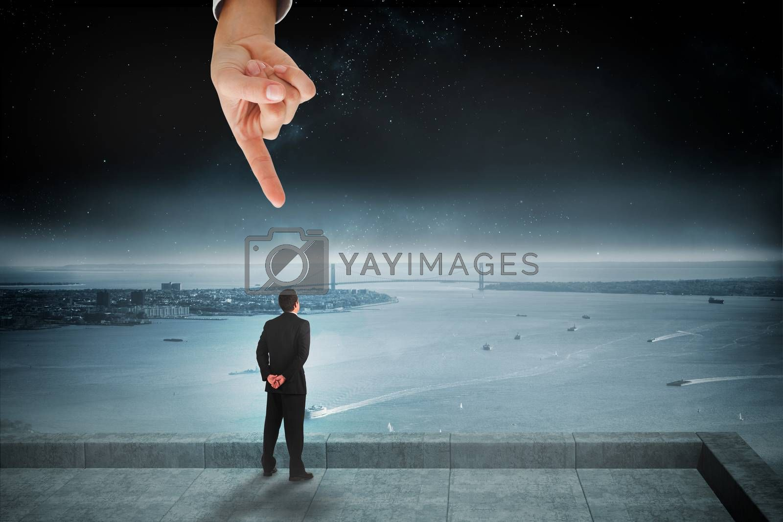 Giant hand pointing at businessman standing and looking by Wavebreakmedia
