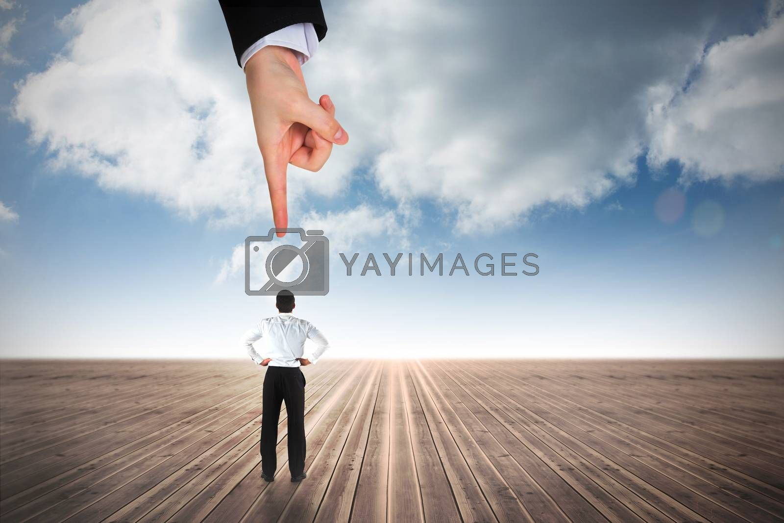 Giant hand pointing at businessman standing back to the camera with hands on hips by Wavebreakmedia