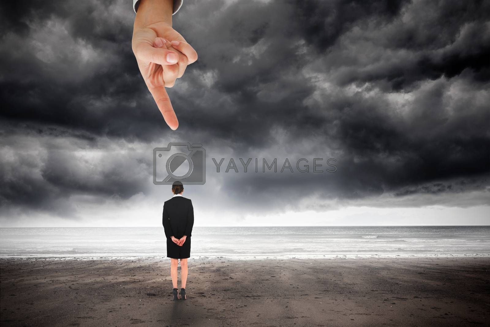 Giant hand pointing at young businesswoman standing with hands behind back by Wavebreakmedia