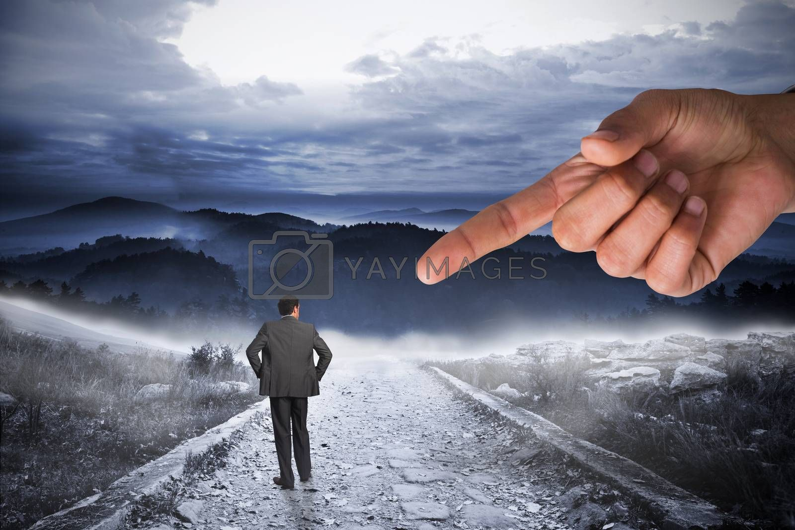 Giant hand pointing at businessman with hands on hips by Wavebreakmedia