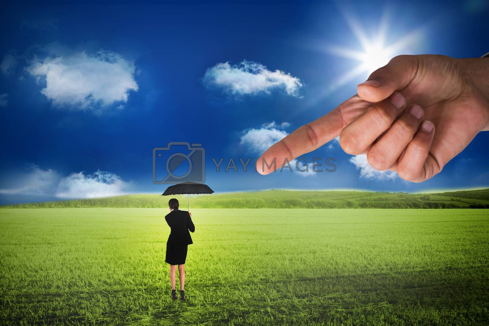 Giant hand pointing at young businesswoman holding umbrella by Wavebreakmedia