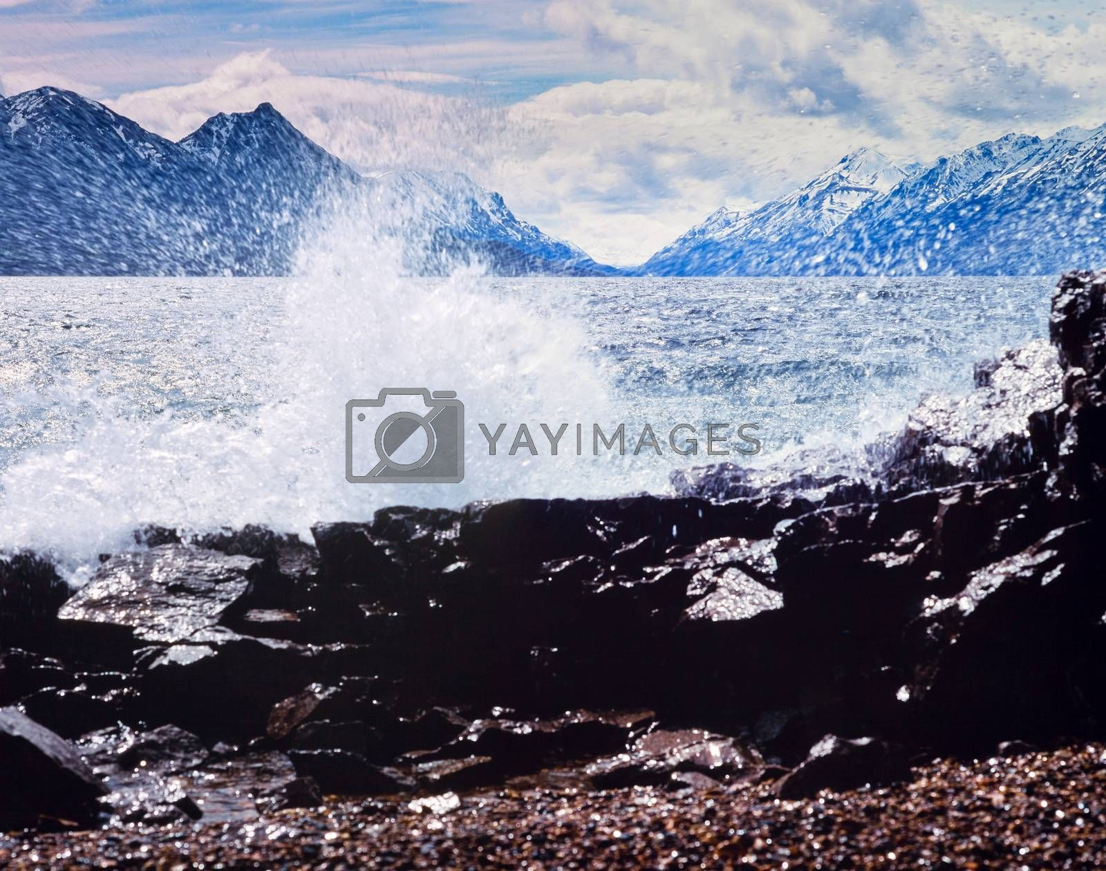 Strong wind and high waves on Lake Bennett rocky shore with distant high mountains on oposite lake side, Yukon Territory, Canada