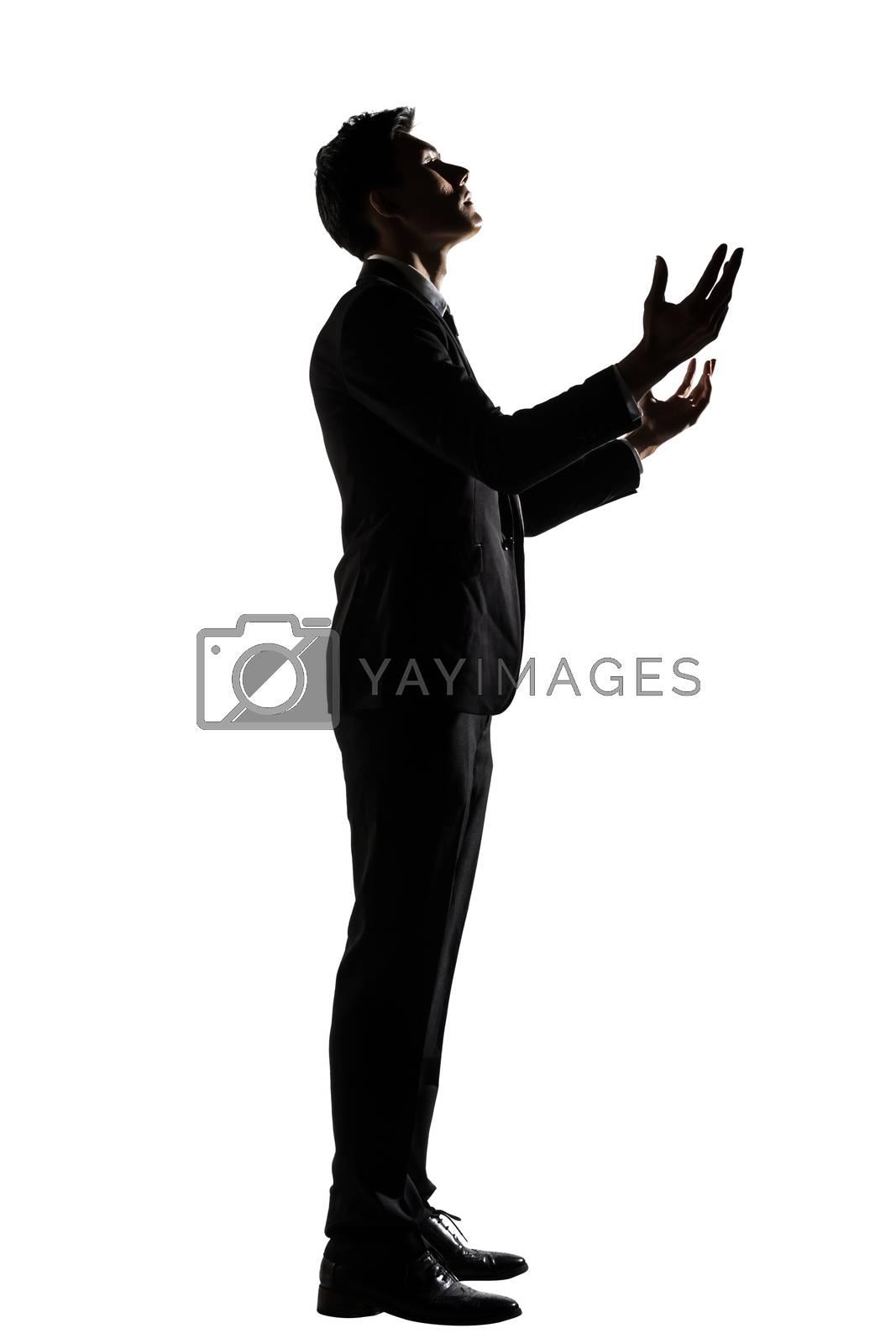 Silhouette of Asian businessman praying by elwynn