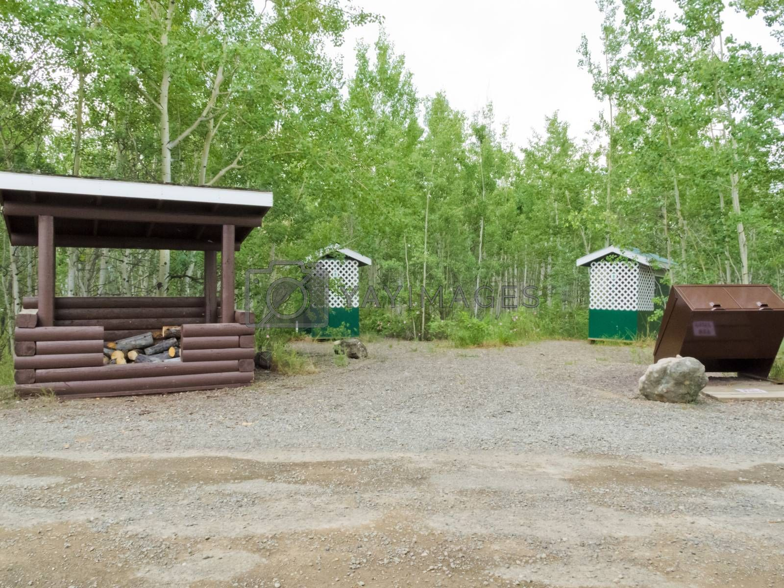 Simple campground facilities, firewood shed, bear-proof garbage bin and pit toilet outhouses on public Yukon Territory Government campground, Yukon, Canada