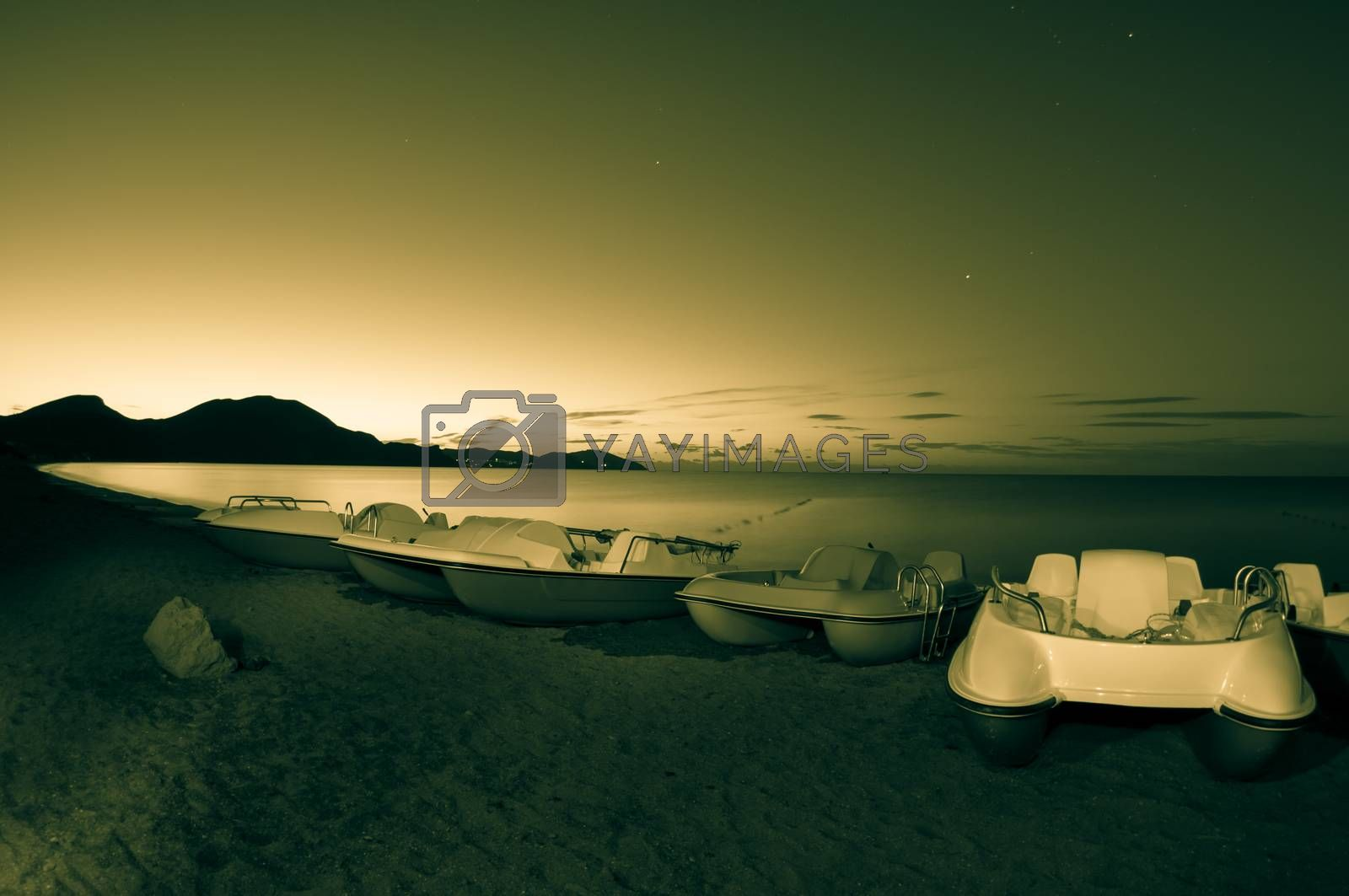 Pedal boats on the beach at night. by bashta