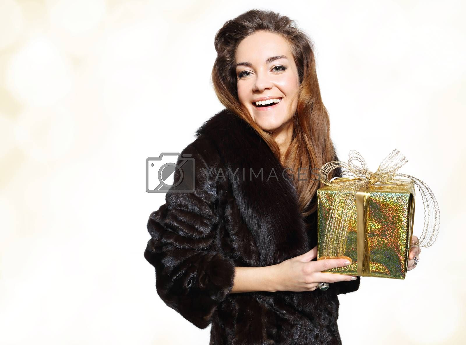 Happy lady in a fur coat with a gold gift by Robert Przybysz