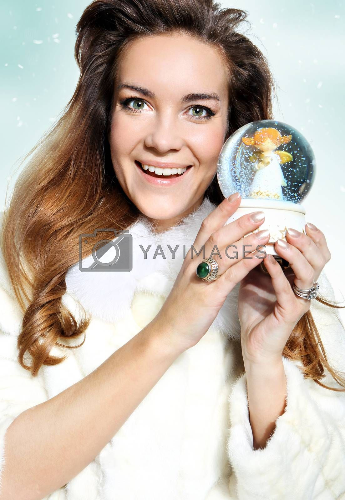 Beautiful happy woman  in a white fur coat  with glass music box by Robert Przybysz