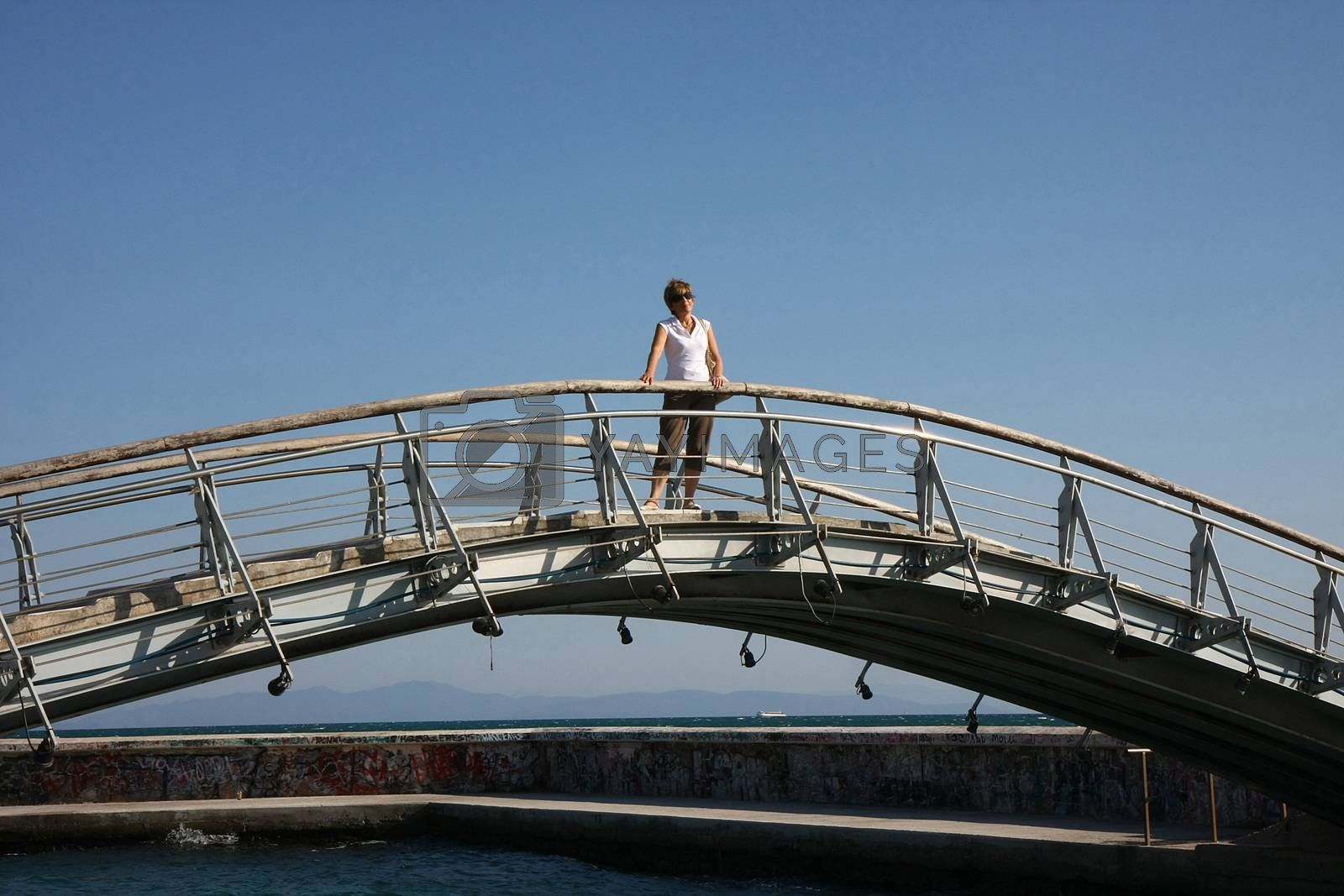 Lady on the bridge connecting two sides of sea breakwater