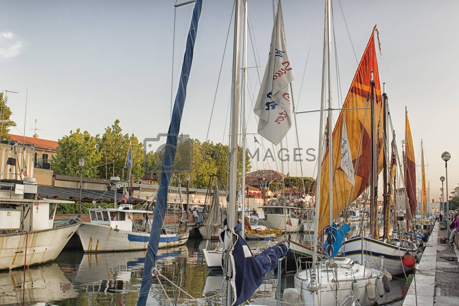 Sailing and engine boats moored in the harbour channel of Cervia in Northern Italy on the Adriatic Sea