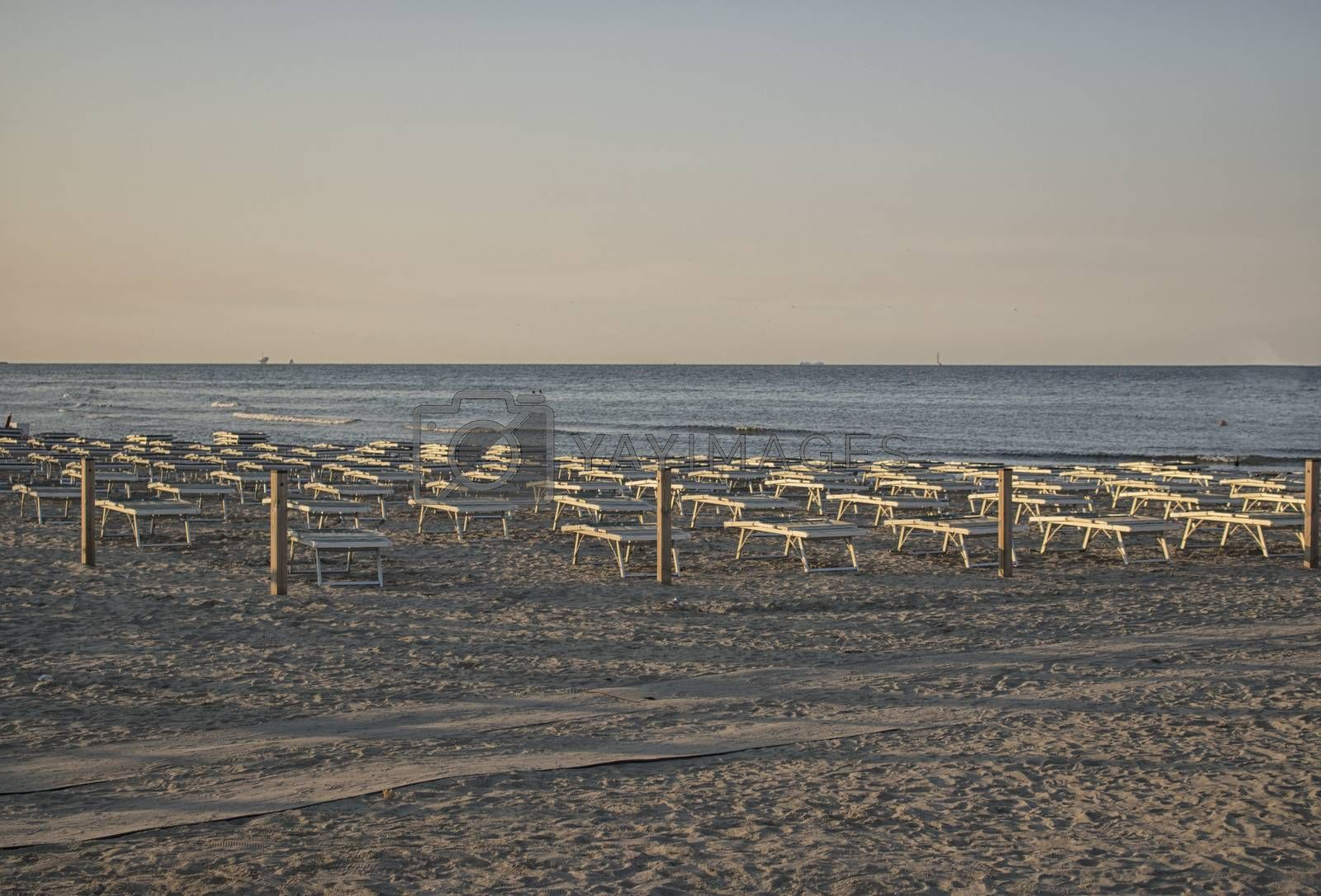 Deckchairs and umbrellas  on the seaside near the harbour channel of Cervia in Northern Italy on the Adriatic Sea