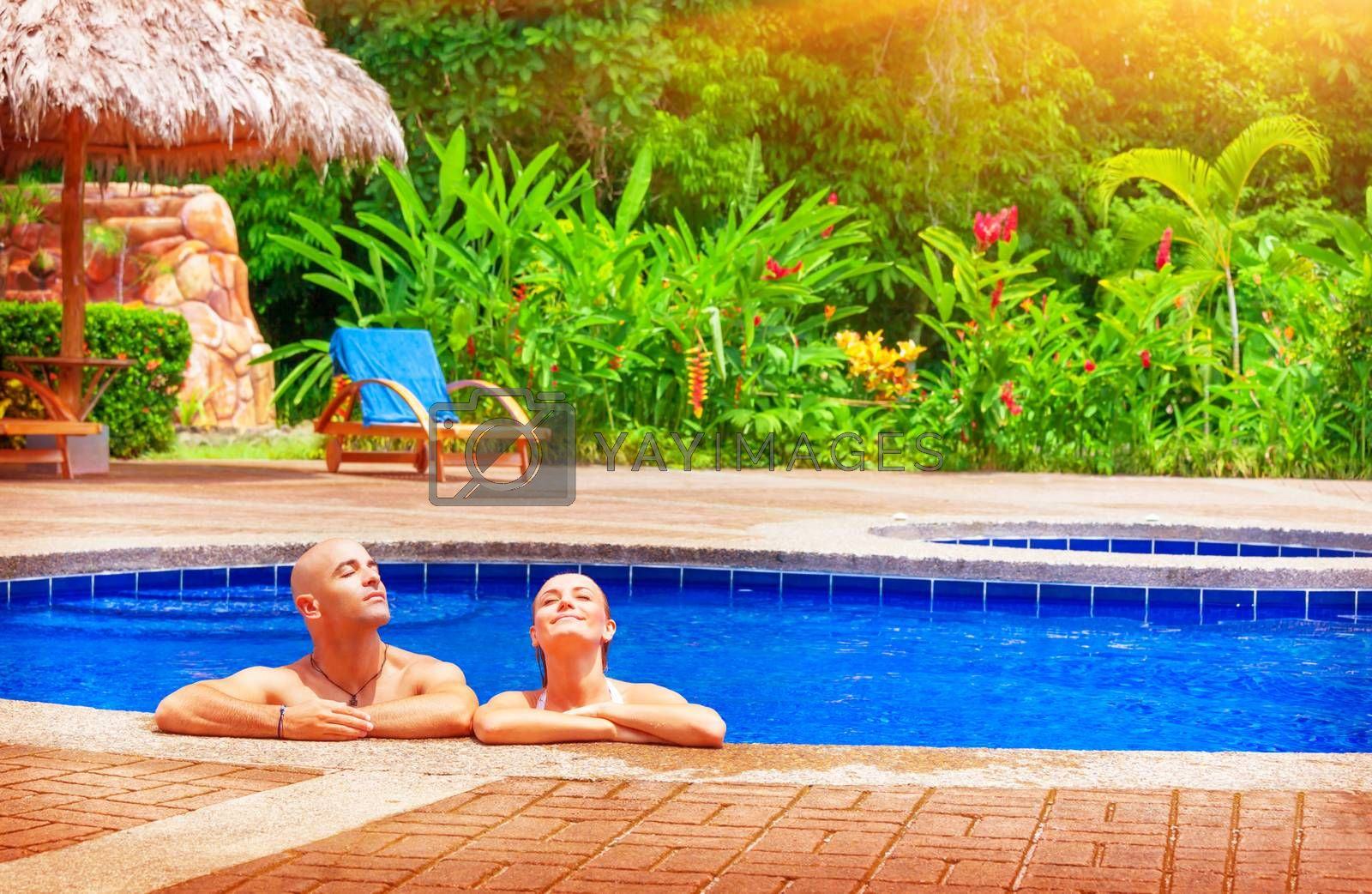 Happy couple enjoying pool, young family on day spa relaxation, luxury vacation on tropical resort, romantic travel destination
