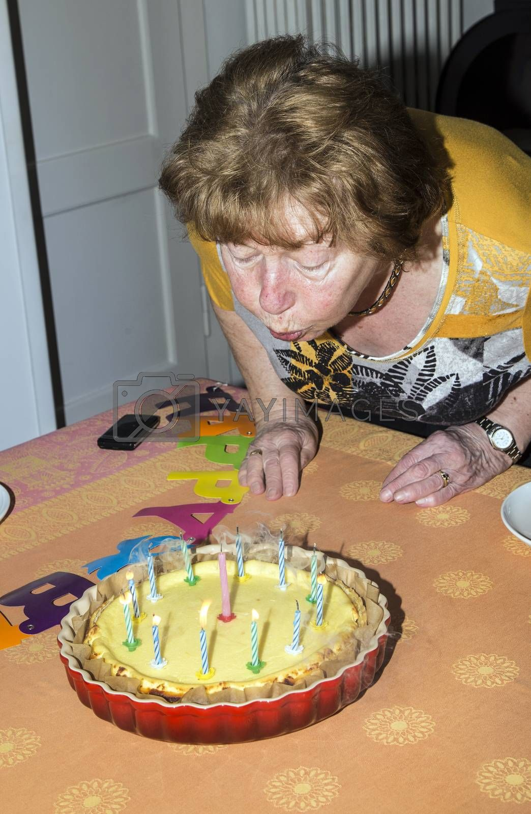 A senior female blows out candles on a cake. Ideal for birthday, anniversary or any other celebration inference.